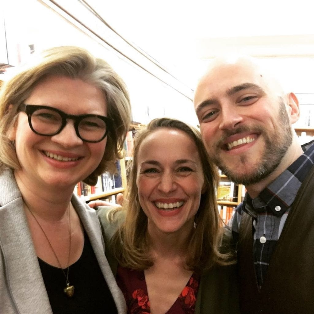 3 people in a bookstore smiling at the camera